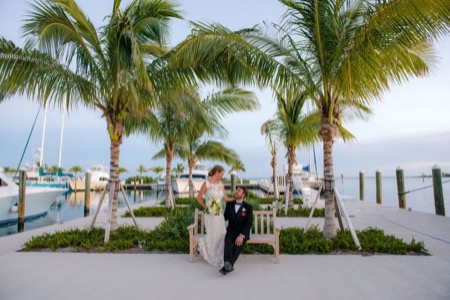 bride and groom sitting on the dock at oceans edge